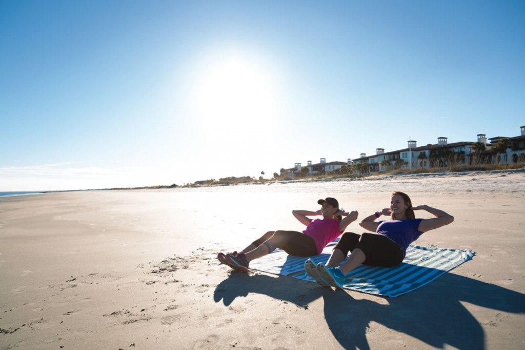 Trish Welch (right), Sea Island personal trainer and fitness instructor, leads a workout on the beach.